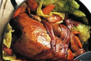 Cast iron pot with a roasted guinea hen with cabbage and bacon
