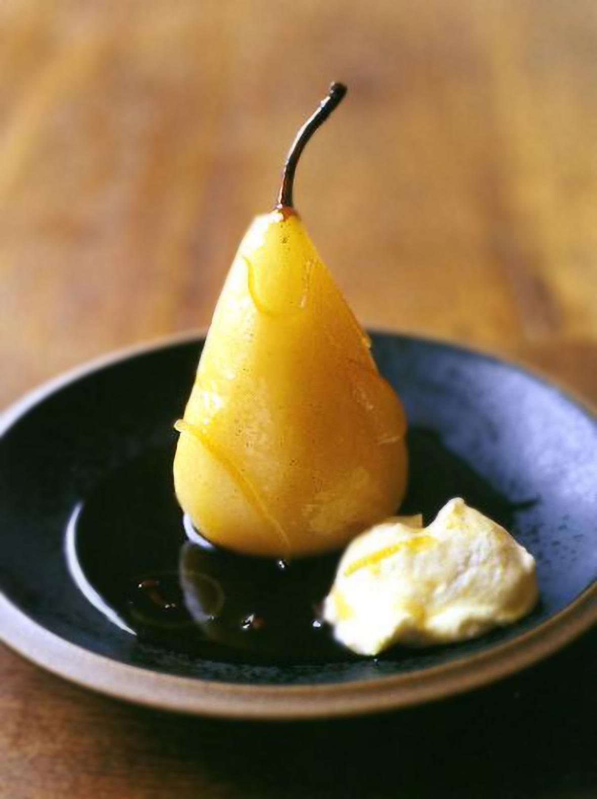 A lemon poached pear with a dollop of lemon cream on a black plate