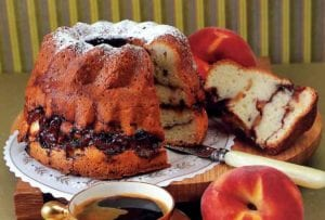 Cake stand with a peach coffee cake--filled with peaches, sugar, and cocoa--and a coffee cup and peach