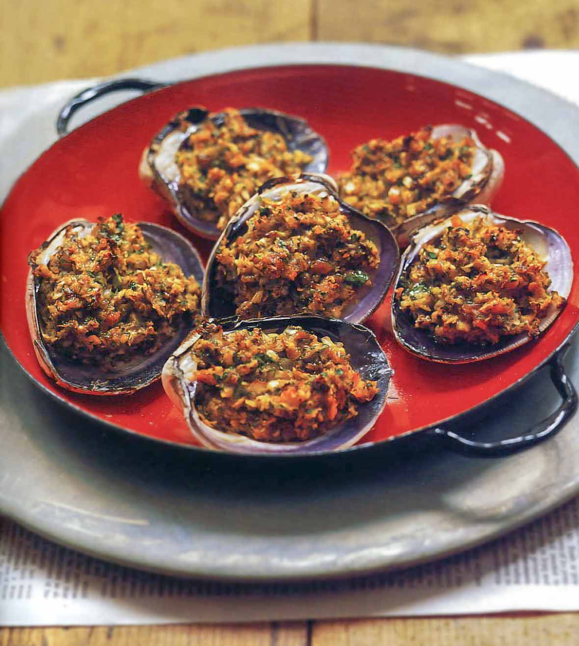 Red plate of six stuffed quahogs clams stuffed with breadcrumbs, chopped clams, parsley, Old Bay Seasoning