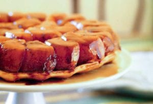 A tarte Tatin, or upside-down caramelized apple tart, on a white cake stand