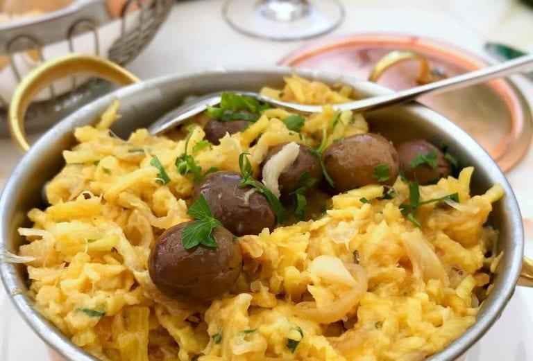 A copper pot of bacalhau a Bras--or Portuguese scrambled eggs, salt cod, potatoes, onions, olives, and parsley