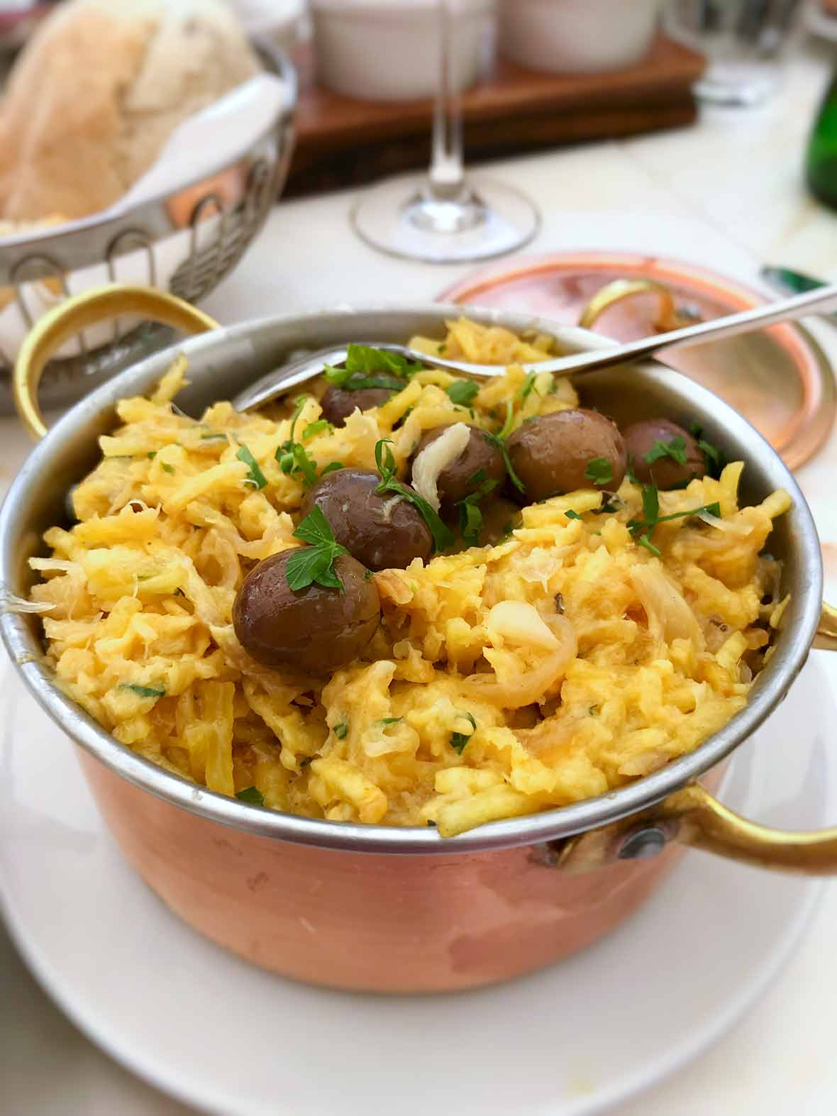 A copper pot of bacalhau a Bras--or Portuguese scrambled eggs, salt cod, potatoes, onions, olives, and parsley