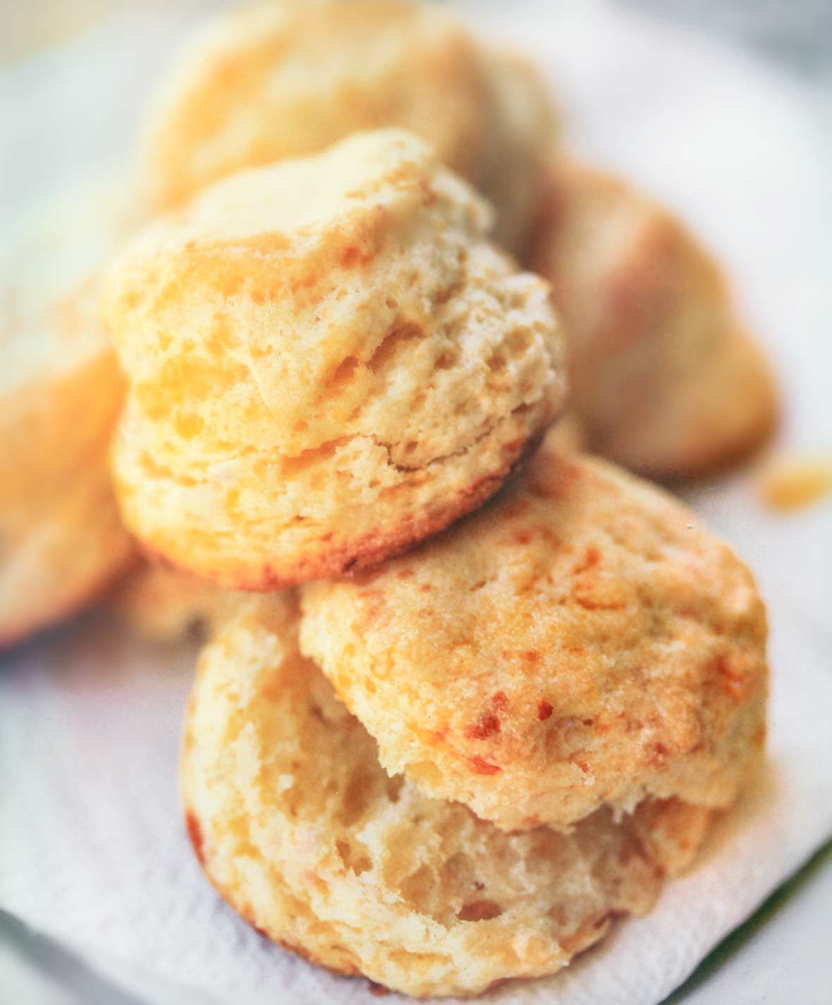 A pile of baking powder biscuits on a white paper napkin