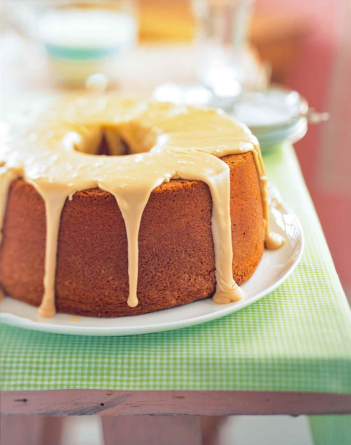 A frosted brown sugar pound cake on a white plate on a cloth-covered picnic table.