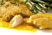 A white plate with a serving of crispy rock cod with citrus sauce and a side of green beans.
