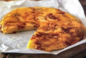 A potato pancake, with cheese and bacon, with a slice missing, on crumpled parchment