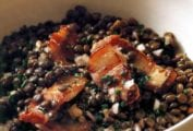 White bowl with warm lentil salad and pieces of bacon