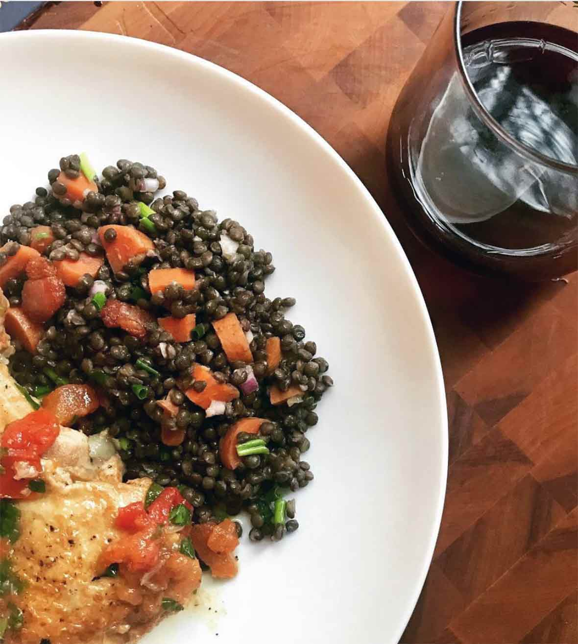 White plate with warm lentil salad and a glass of wine