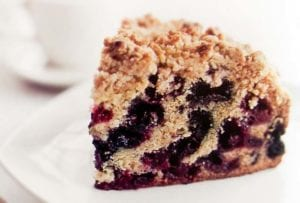 A slice of blueberry buckle with layers of blueberries and a crumb topping of butter, flour, sugar, cinnamon, and ginger