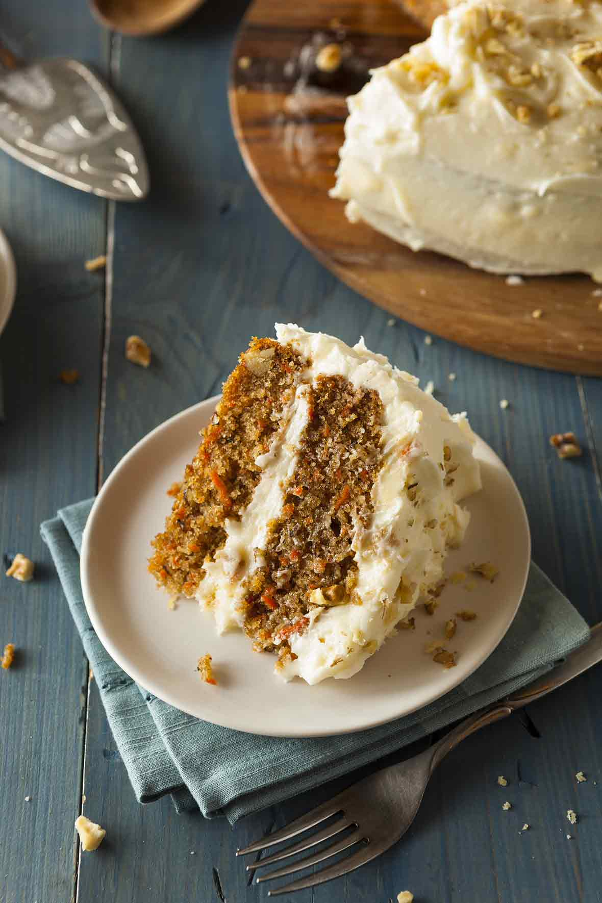 A slice of classic carrot cake--two carrot cake layers filled and frosted with cream cheese frosting; on top are crushed walnuts