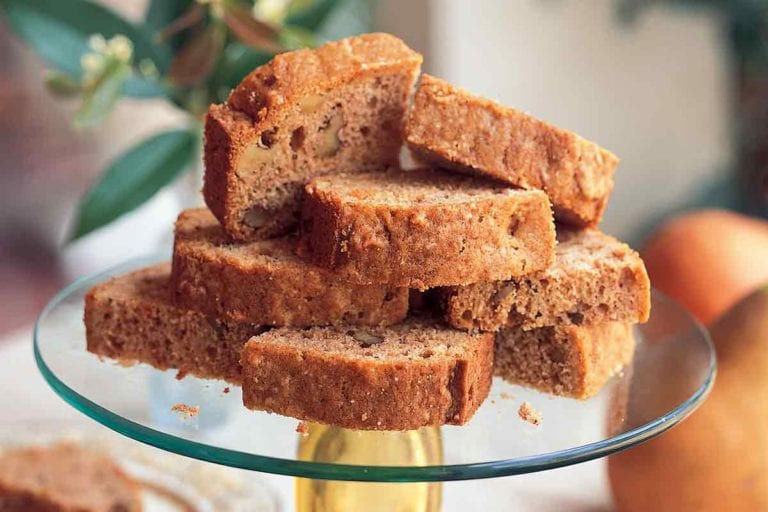 A glass cake stand topped with several slices of Cornelia Walker Bailey's pear bread.