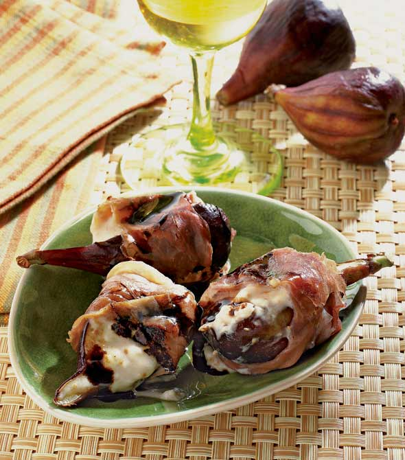 A green plate of grilled fresh figs with country ham wrapped over mascarpone cheese, and blue cheese