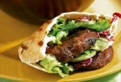 A bowl of grilled portobello burgers in pita bread with mixed greens and one on a plate