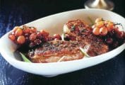 Grilled duck breasts with roasted grapes and potato-bacon gratin on a white plate on black background