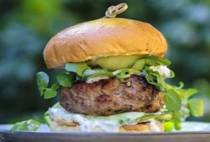 A juicy grilled lamb burger topped with feta cheese, tzatziki, pickles on a bun