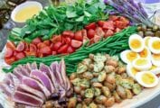 Platter of nicoise salad with slice tuna, roasted potatoes, sliced eggs, green beans, tomatoes, and greens