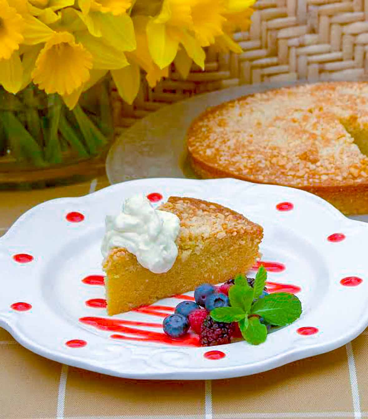 Slice of olive oil cake topped with a dollop of lemon curd on a white plate with red dots and squiggle of berry coulis