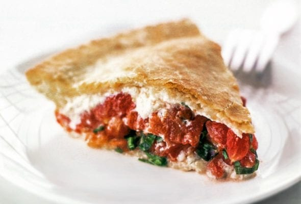 A wedge of tomato pie on a white plate with a fork in the background.