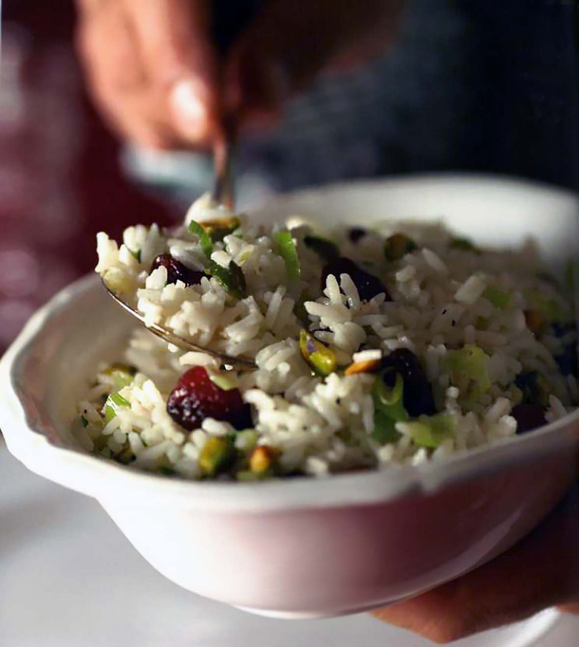 White bow of rice pilaf, dried cherries, and pistachios being stirred