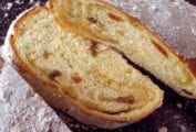 A loaf of stollen cut in half, with one slice cut off to show the fruit and marzipan filling.