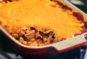 Casserole dish of turkey chunks, black beans, topped with Cheddar cheese