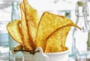 White bucket filled with rustic golden brown Parmesan flatbreads on a plaid napkin