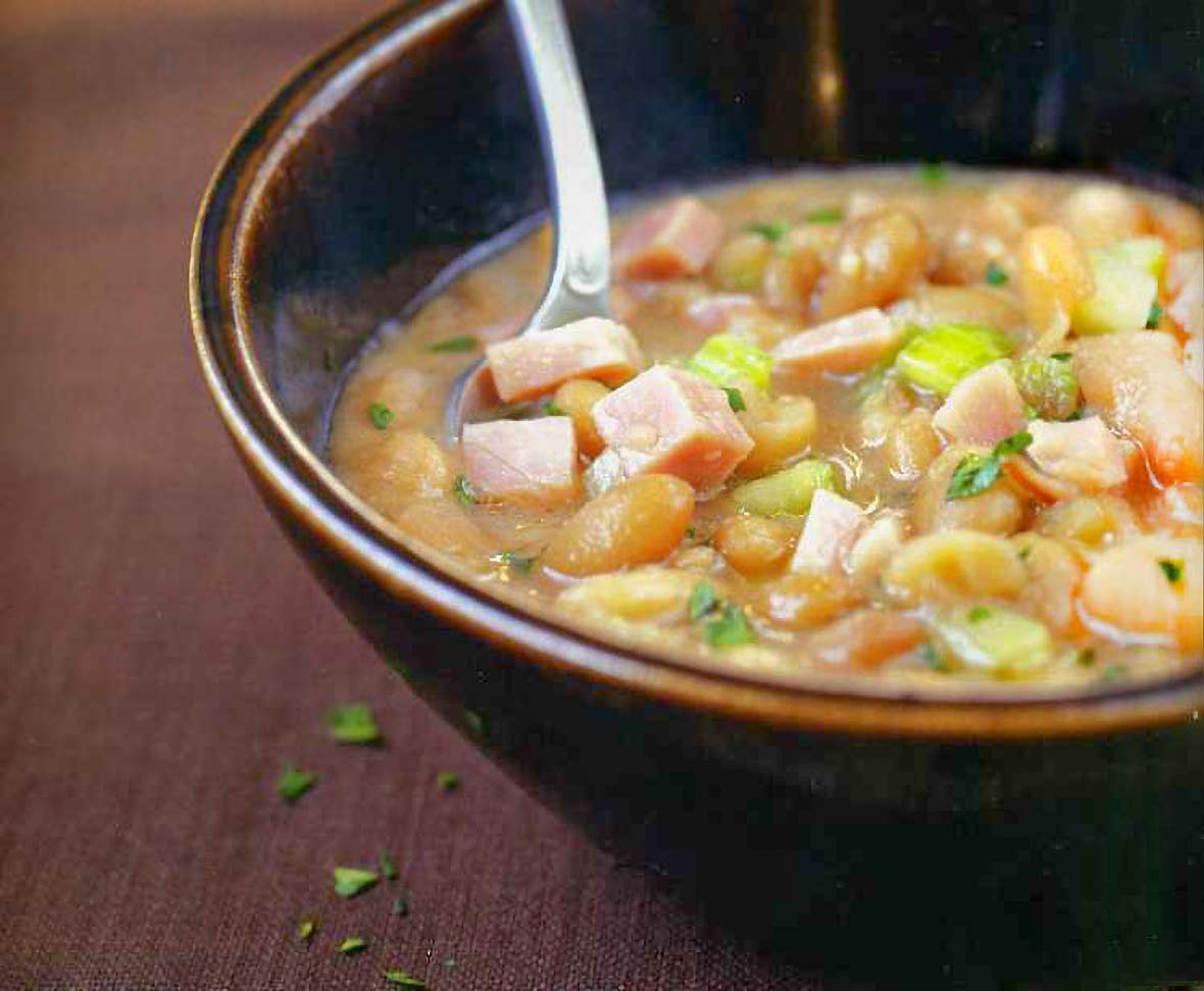 Bowl with a soup of navy beans, ham hocks, onions, celery, and parsley on brown fabric