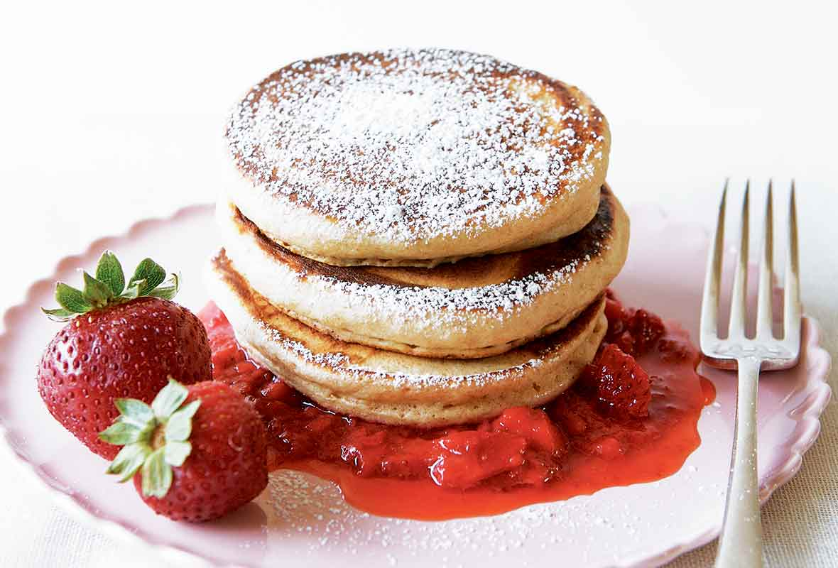 A stack of three whole-wheat pancakes with strawberry sauce, a couple whole strawberries, and confectioners' sugar sprinkled over the top.