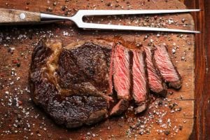 A Delmonico steak on a wooden cutting board with a meat fork resting beside it.