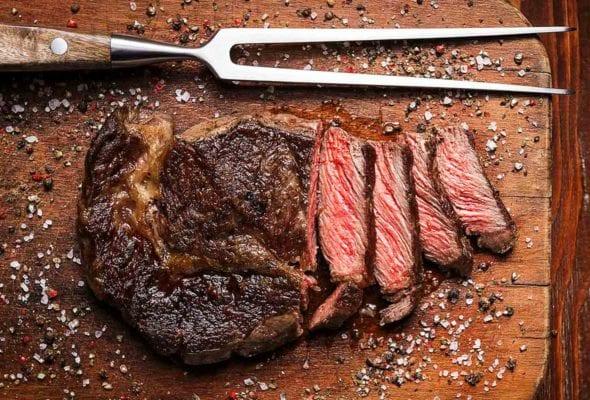 A Delmonico steak on a wooden cutting board with a meat fork resting beside it.