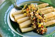 White asparagus salad topped with diced red, yellow, and green peppers on a green plate, wine nearby