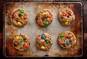 A baking sheet with six peanut butter-oatmeal-chocolate chip cookies studded with M&Ms