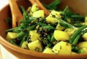 A wooden bowl of green bean and potato salad with pesto, almonds, and tomato
