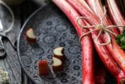 A bunch of rhubarb stalks tied together with twine on a black platter for use in rhubarb with berries and candied ginger