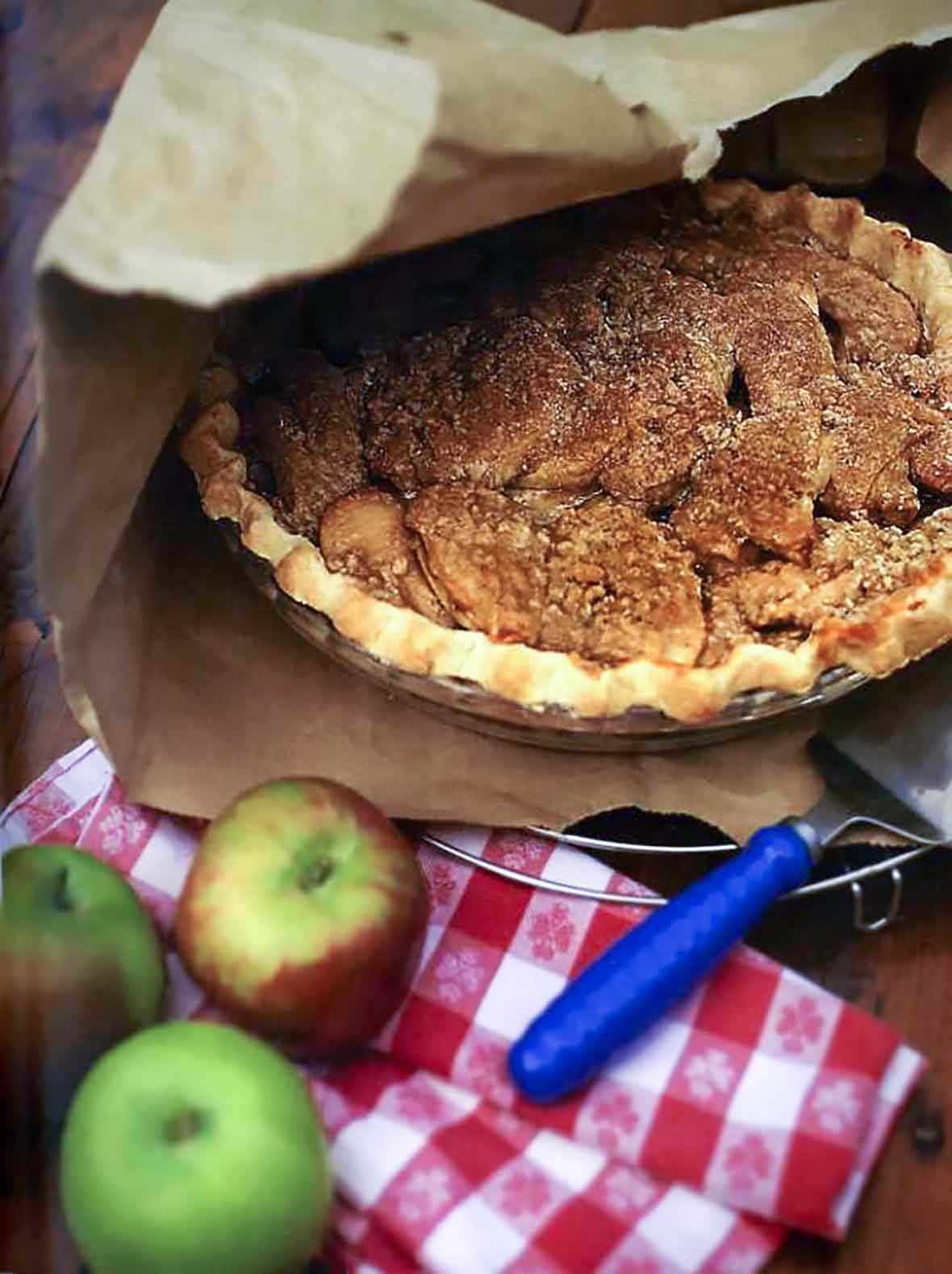 A cooked brown-bag apple pie inside a torn paper bag