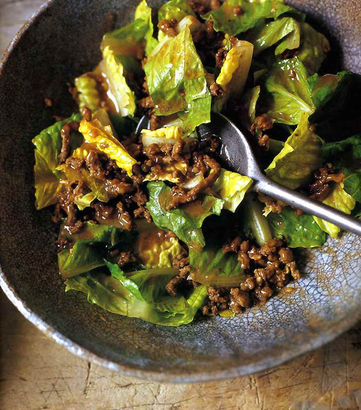 Ceramic bowl of romaine lettuce with hot beef dressing, garlic, and ginger