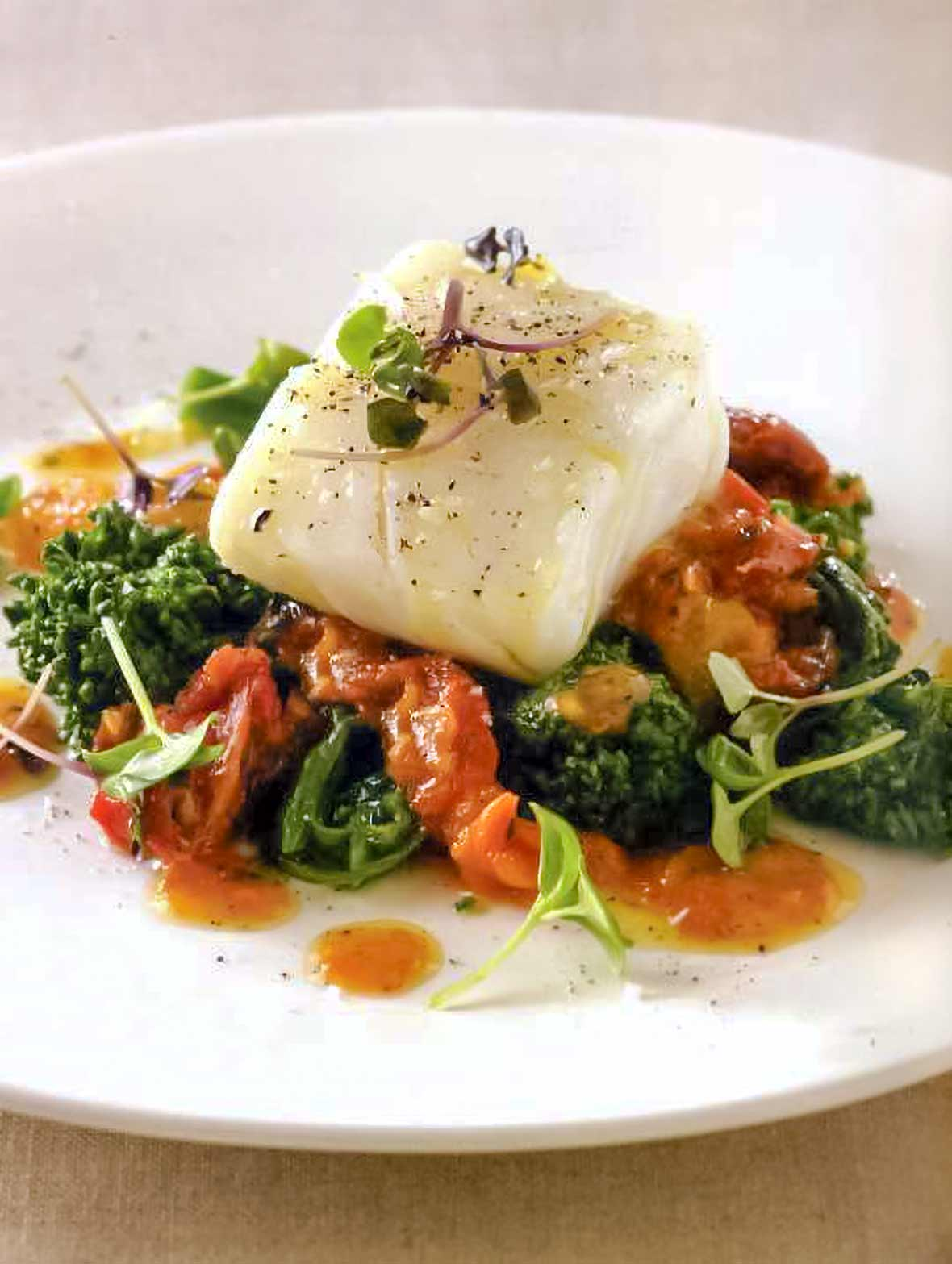 A fillet of olive oil poached cod atop tomato and broccoli rave in a white plate