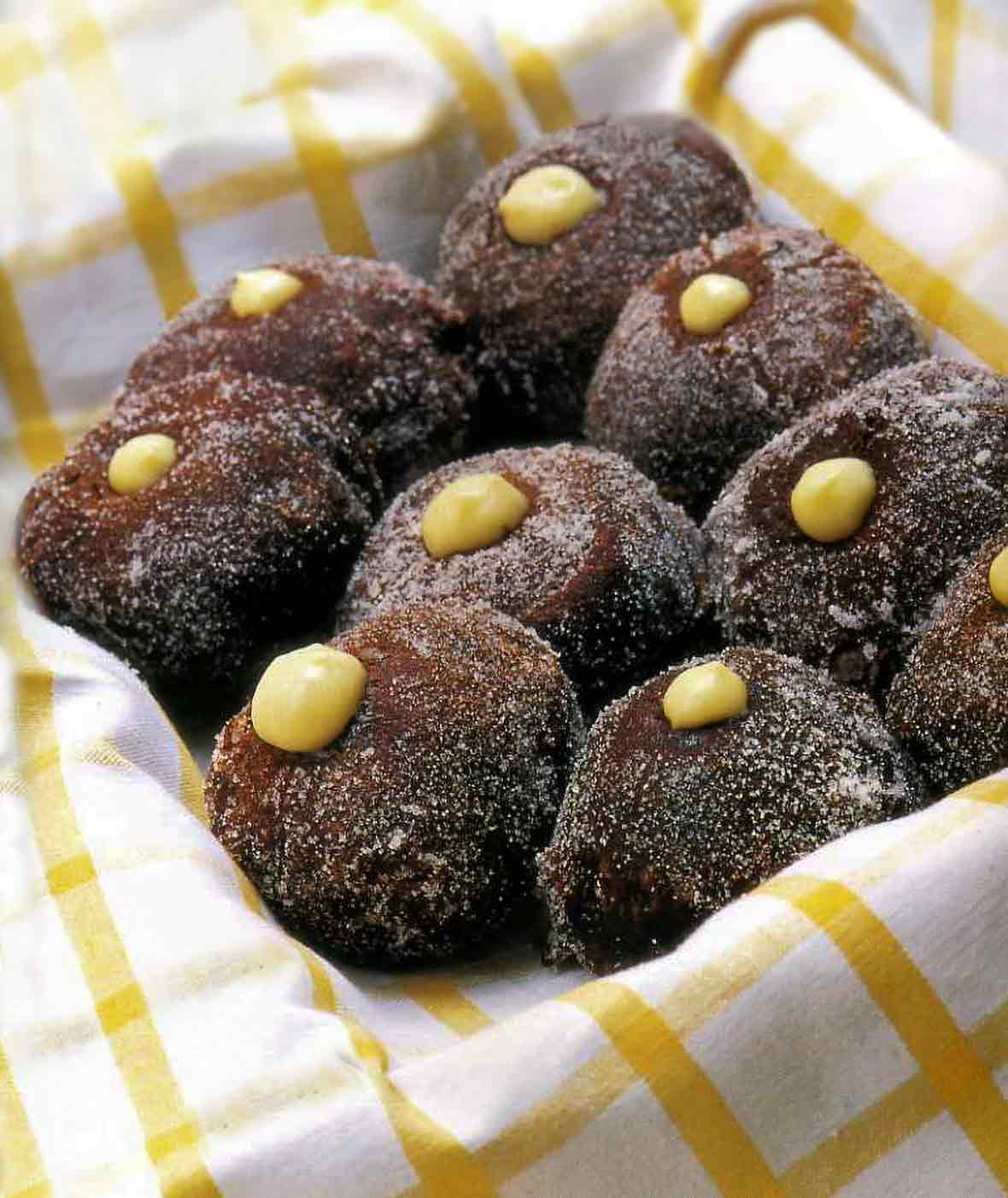 Napkin-lined basket of 9 cream-filled chocolate doughnuts with a dot of pastry cream on each