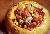 Lamb tagine in a whole roasted pumpkin with the top removed; inside chunks of lamb, pumpkin, tomato, chickpeas