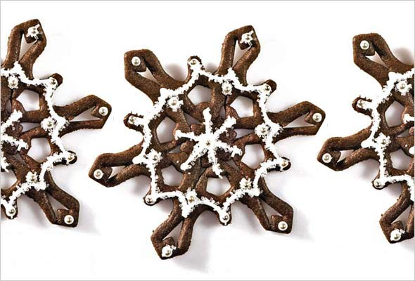 Three spicy snowflake cookies on a white background.