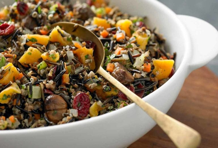 A white bowl of wild rice, roasted chestnuts, and cranberries with a gold spoon resting inside.
