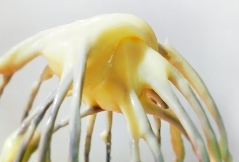 A whisk with homemade mayonnaise on it