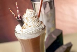 Tall glass filled with a chocolate milkshake, topped with whipped cream, chocolate shavings, three straws