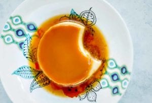 Portuguese tea flan with a caramel top and a puddle of caramel on a white plate with blue design