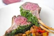 White plate with roasted rack of lamb with parsley, dijon, and chives, ratatouille nearby