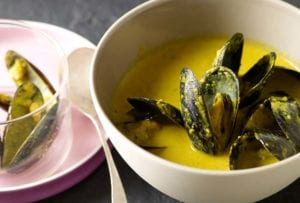 Bowl of saffron mussel stew with a yellow broth, a plate with shells to the left