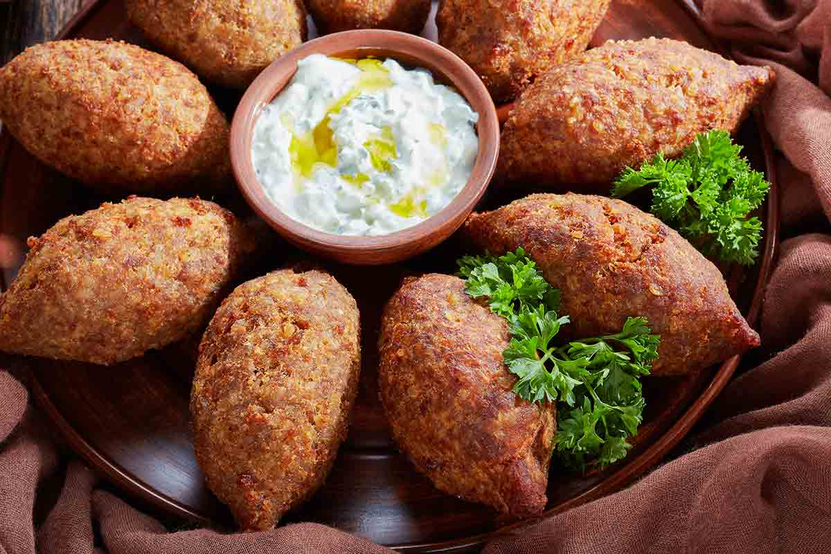 A platter of Brazilian beef kibbe with a cup of yogurt mint dressing in the center and cups of pine nuts and peppercorns, and a head of garlic on the side.