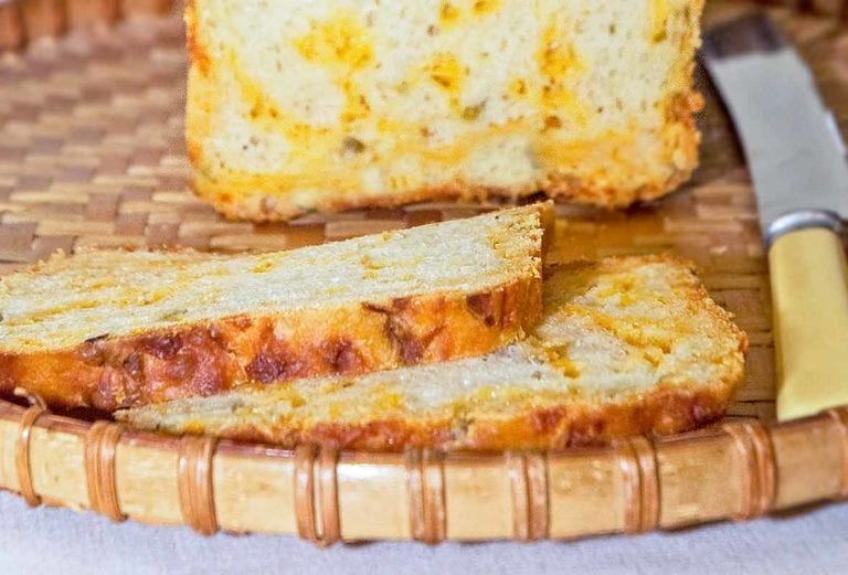 A loaf of Cheddar and chiles bread, with two slices cut, on a wicker tray