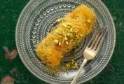 An rectangular dessert wrapped in thin stands of pastry, topped with crushed pistachios on a glass plate